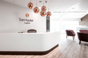 Larchpoint Capital Logo with copper light fixtures above a reception desk.