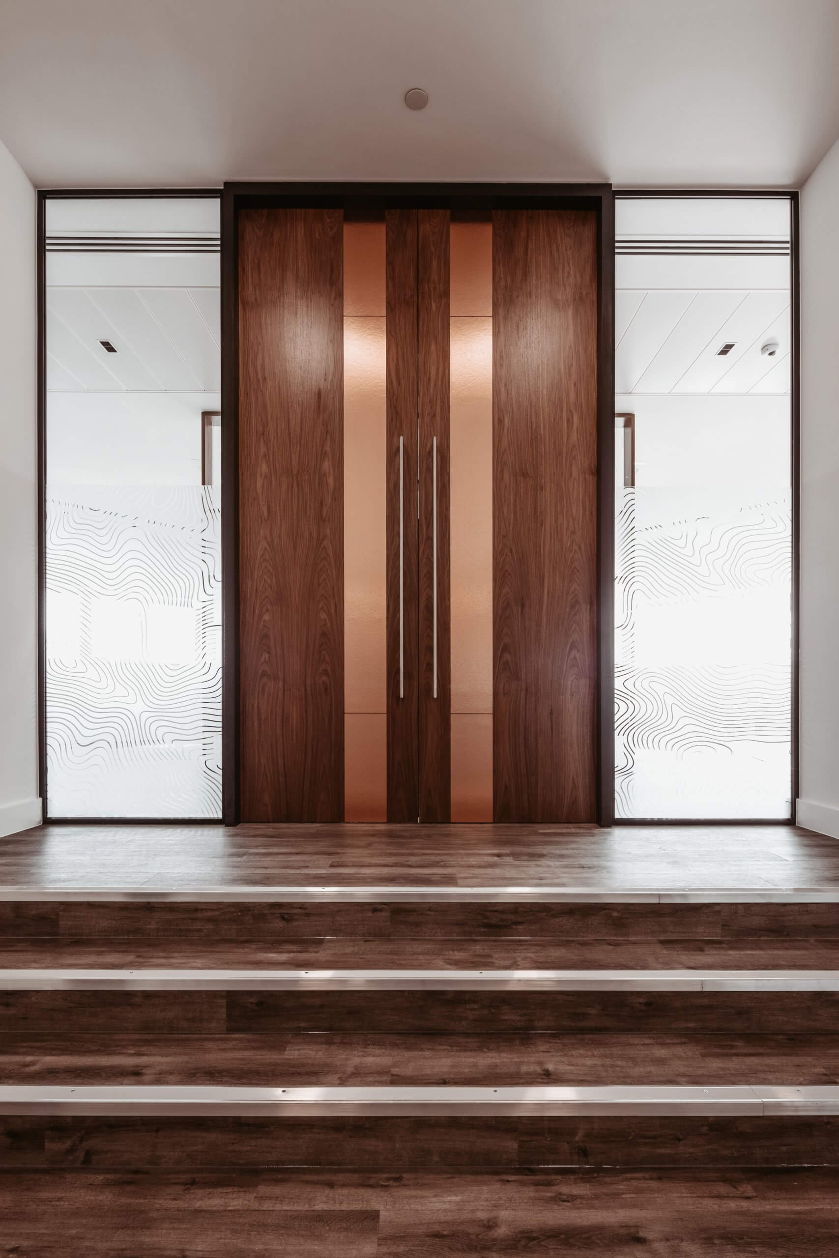Walnut door with copper inset and privacy film